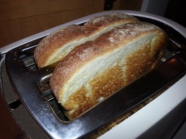 """A picture of a toaster with toasted bread. Featured image for """"How Does a Toaster Work"""""""